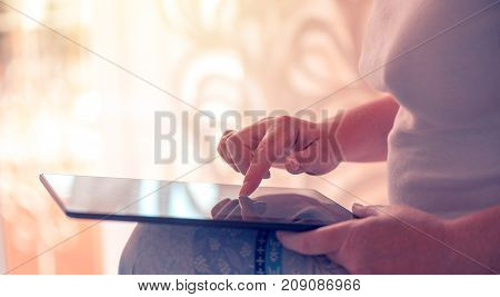 Close up of female hand and finger pushing digital tablet touch screen. Woman using modern electronics for internet browsing. Lifestyle and technology concept.