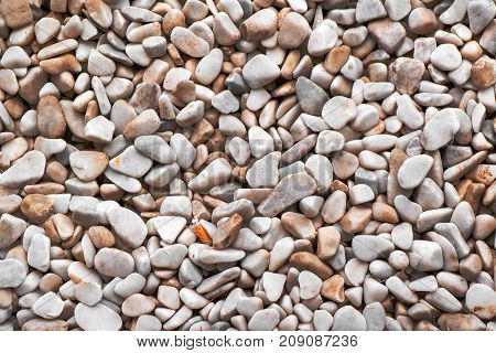 Natural abstract pebbles background top view of surface covered with small stones