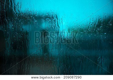 Raindrops on window glass surface. Drops of rain as abstract autumn season background.