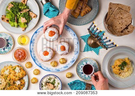Jewish holiday Hanukkah, traditional feast, hands above table top view horizontal
