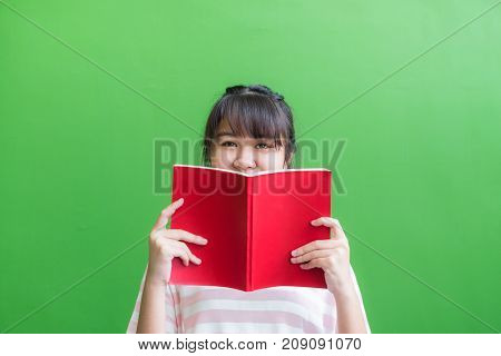 teenager asia girl holding red book cover face with thinking action against green vivid wallLeave copy space upper head to adding content of design for advertising education campaign concept..