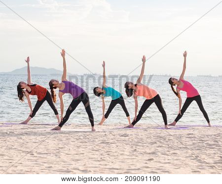 Yoga class at sea beach in evening Group of people doing Triangle poses with clam relax emotion at beachMeditation poseWellness and Healthy balance lifestyle