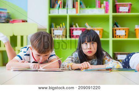 Two kid lay down on floor and reading tale book in preschool libraryKindergarten school education concept.