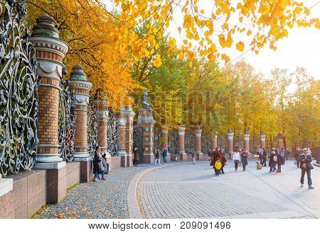 SAINT PETERSBURG RUSSIA - OCTOBER 3 2016. Fence of the Michael Garden in Saint Petersburg Russia and tourists walking along