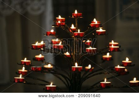 Flame Burning Candles In A Catholic Cathedral.