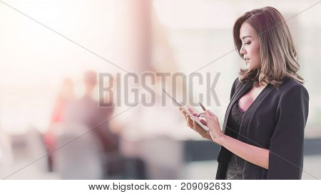 Beautiful sexy Asian businesswoman using tablet in office space background and copy space.Concept of business meeting.Vintage tone