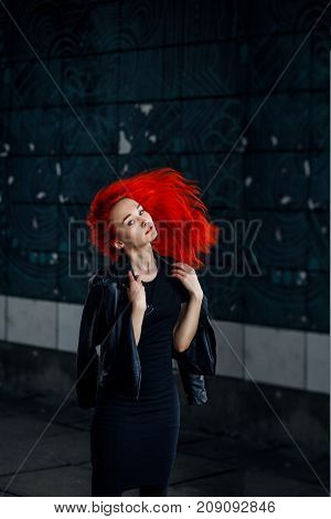 Expressive Redhead woman posing at dark wall and her hair flying against black background.
