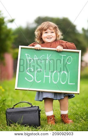 Cute caucasian little girl holding chalkboard written back to school. With a smile. Ready and happy back to school. Fall outdoors autumn day education concept back to school concept. Early developement early education.
