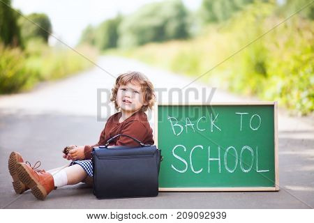 Cute toddler girl wearing school uniform with back to school blackboard wautung gor a school bus. Fall outdoors education concept sunny autumn day. Early education little genius wunderkind concept.