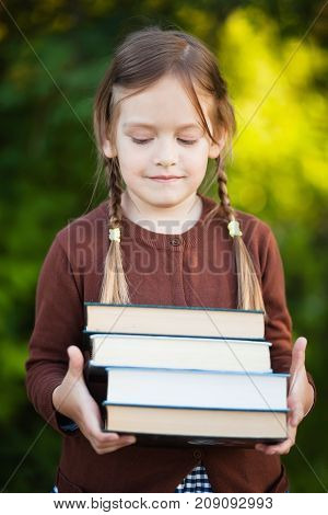 Adorable happy little preschooler girl with pigtails ready back to school holding pile of textbooks manuals. Wearing school uniform. Warm september fall day. Smart clever intellegent little girl.