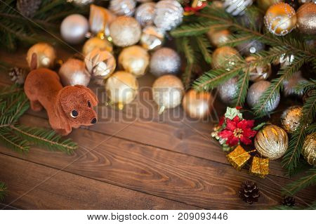 Year of the dog. Dog with a gift on a wooden background. Christmas balls pine cones a composition of the new year in golden color. The year of the dog on a horoscope symbol. Copyspace emptu space for text.