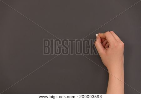 A teacher about to write on the chalkboard