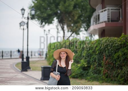 Young stylish woman arriving at hotel near the sea.