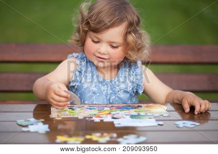 Blonde toddler girl solving puzzle on a table having fun. Early education and developement. Little genius concept.