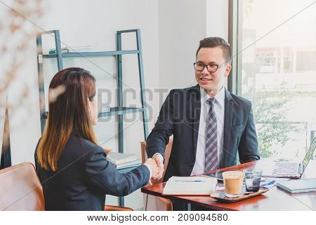 Asian Businessman making handshake with a businesswoman at office space - greeting and dealing concepts