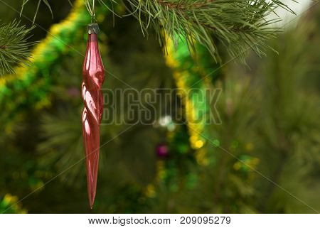 vintage glass Christmas ornament - red icicle - on a background of a blurred Christmas tree