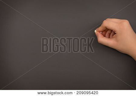 A close up of a teacher about to write on the chalkboard