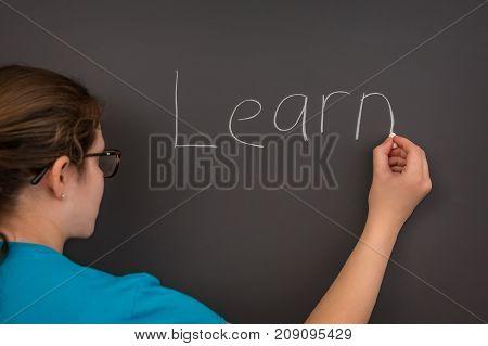 A teacher writing the word learn on the chalkboard