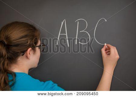 A teacher writing the ABC's on the chalkboard