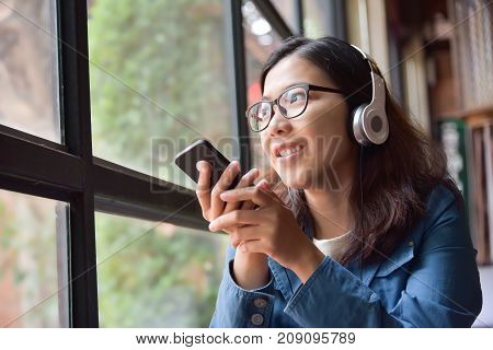 Happy Beautiful Asian woman in blue shirt sitting next to the window while listening to the music with headphone via her smart phone at coffee shop.