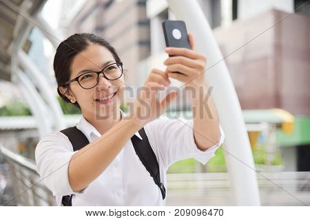 Chinese Woman wear glasses in white shirt taking photo with her smart phone. Copy space.