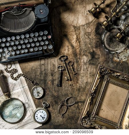 Antique typewriter and vintage office tools on wooden table. Nostalgic still life