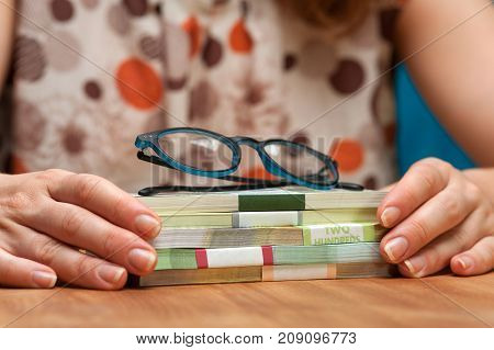 Closeup of female sitting at the table with currency heaps and eyeglasses.