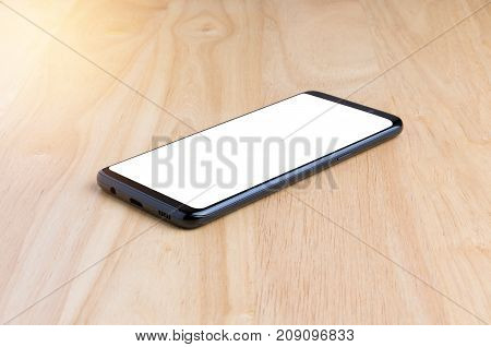 Black Smart Phone With White Screen On The Wooden Table