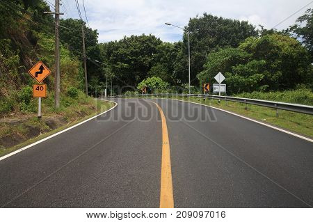 curve uphill road and yellow street zigzag sign with 40 miles speed limit. Success milestone concept to reach upper goal