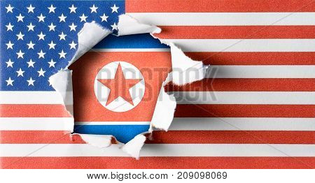 Ripped USA and United States of America flag on rough paper texture with North Korea flag in the hole.