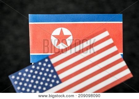 The flag of North Korea and United States of America (USA) made from paper on wooden stick against dark background.