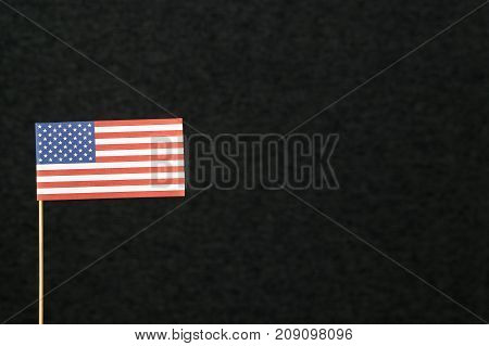 The flag of United States of America (USA) made from paper on wooden stick against dark background with negative copy space for text.
