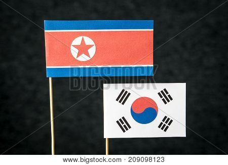 The flag of North Korea and South Korea made from paper on wooden stick against dark background.