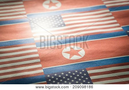 The flag of North Korea and United States of America (USA) on a wrinkled rough paper texture.