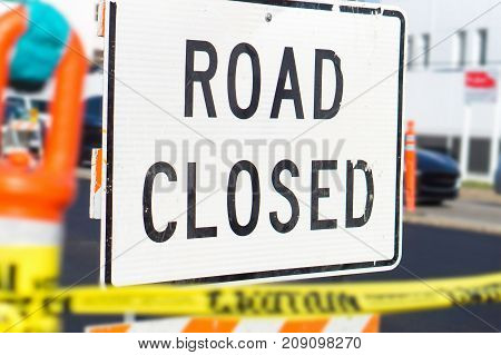Road closed sign and block in a busy city street in the middle of traffic. Roadblock in a highway.