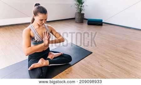 Young woman doing yoga at home in the lotus position. Healthy female sitting on exercise mat with legs crossed and hands joined indoors.