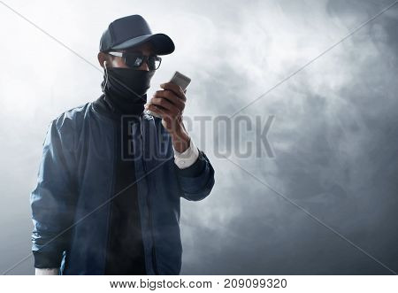 Unknown hacker use mobile phone on smoke background