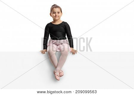 Little ballerina sitting on a panel and looking at the camera isolated on white background