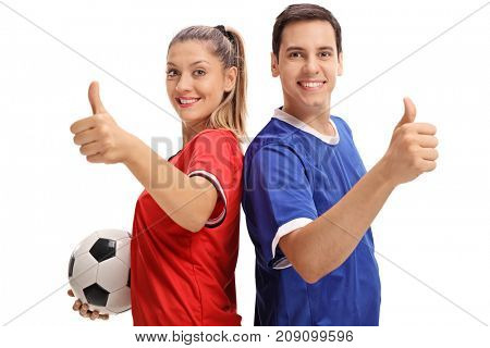 Female and a male soccer player holding their thumbs up and smiling isolated on white background