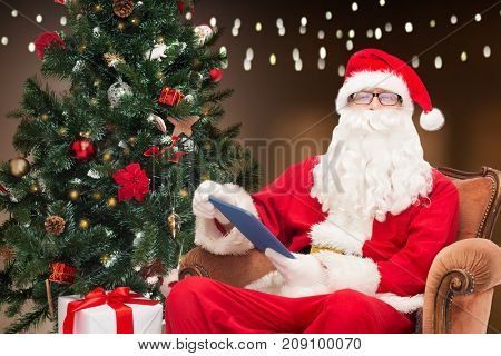 technology, holidays and people concept - man in costume of santa claus with tablet pc computer, gift and christmas tree sitting in armchair over garland lights background