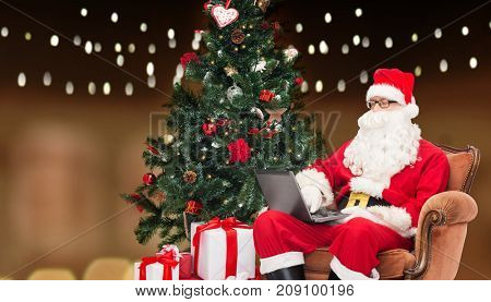 technology, holidays and people concept - man in costume of santa claus with laptop computer, gifts and christmas tree sitting in armchair over garland lights background
