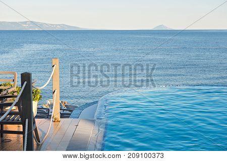 Empty azul infinity pool on the sunset, quiet bue sea