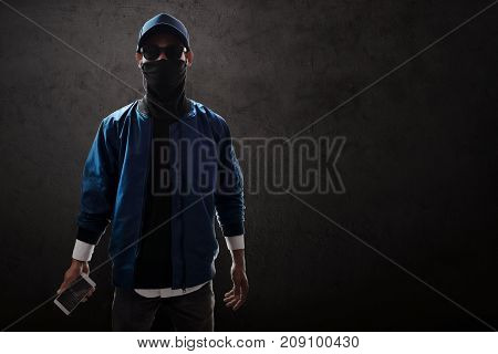 Unknown hacker standing and holding mobile phone
