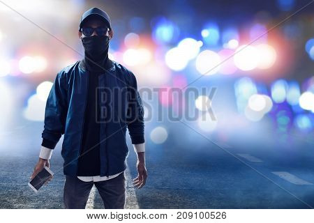Unknown hacker holding mobile phone on the street