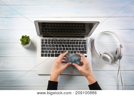 Woman using laptop and credit card for online shopping on wooden background