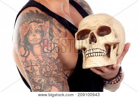 Guy with tattooes holding a human skull isolated on a white background