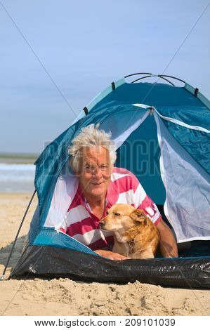 Man and dog camping in tent at the beach