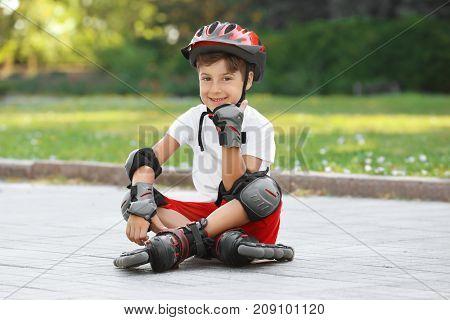 Cute boy on roller skates sitting in park