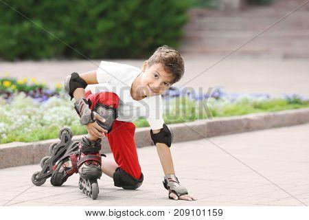Cute boy on roller skates in park