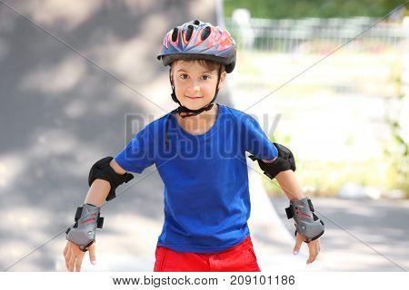 Cute boy rollerblading in skate park